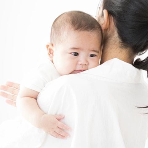 ママに背中を撫でてもらう赤ちゃん